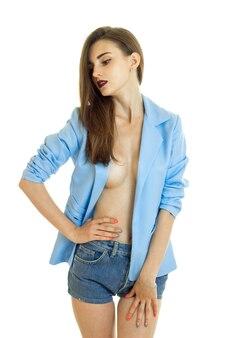 Verführerische junge brünette in blauer jacke ohne bh unter isoliert auf weißem hintergrund