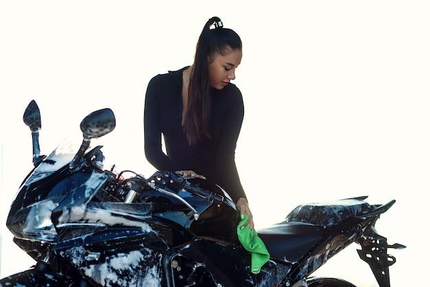 Verführerische junge frau, die stilvolles sportmotorrad wäscht und es vom purpurroten schaum abwischt. kümmere dich um das fahrzeug.