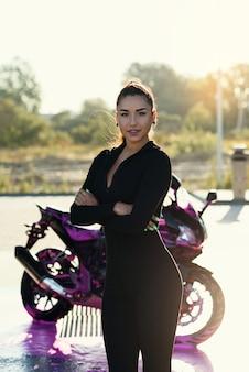 Verführerische junge frau im eng anliegenden schwarzen anzug wirft nahe sportmotorrad bei selbstbedienungsautowaschanlage auf