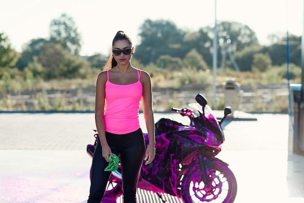 Verführerische junge frau im rosa t-shirt wirft nahe sportmotorrad an selbstbedienungsautowaschanlage in der auf