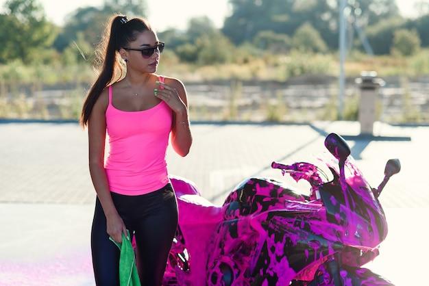 Verführerische junge frau im rosa t-shirt wirft nahe sportmotorrad bei selbstbedienungsautowaschanlage in auf