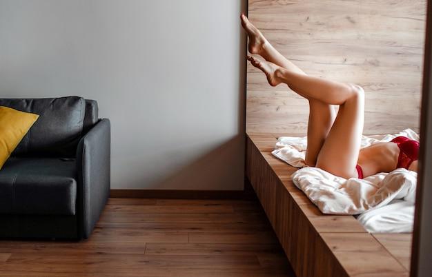 Verführerische junge nackte dunkelhaarige frau im bett am morgen. schnittansicht des gut gebauten schlanken heißen sexy modells liegend und posierend. schöne beine. allein im zimmer.