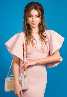 Verführerische junge stilvolle sexy frau im rosa luxuskleid, sommermodetrend, schicker stil, blauer studiohintergrund, hält trendige handtasche