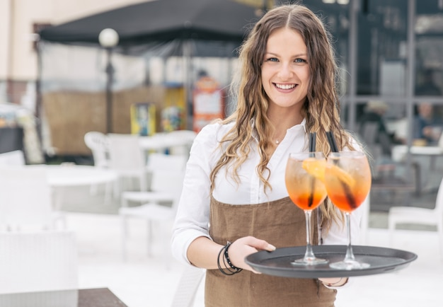 Verführerische kellnerin bringen aperitif zum kunden