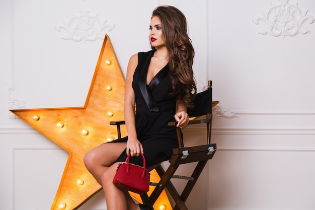 Verführerische modische frau im eleganten schwarzen kleid und im erstaunlichen schmuck, der auf stuhl sitzt