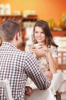 Verführerische schönheit, die ihren liebhaber mit kaffeetasse betrachtet. romantisches gespräch haben