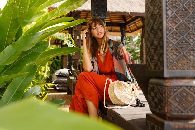 Verführerische stilvolle frau in böhmischer sommerkleidung, die im tropischen luxusresort aufwirft. urlaubskonzept.