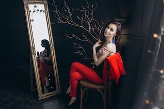 Verführerische Frau im roten Anzug sitzt vor einem Spiegel