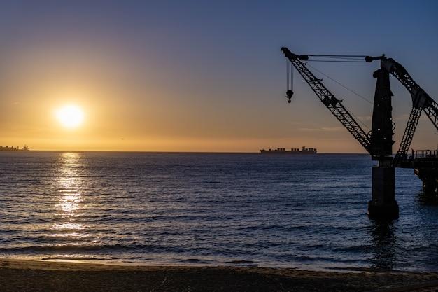 Vergara-hafenkran bei sonnenuntergang mit einem seeschiff