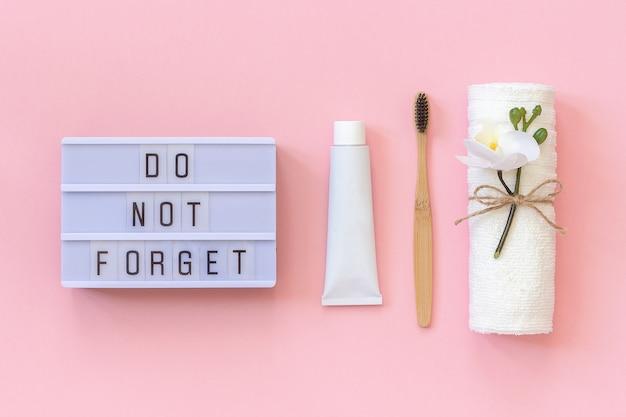 Vergessen sie nicht eine natürliche, umweltfreundliche bambusbürste für zähne, handtuch, zahnpastatube. set zum waschen