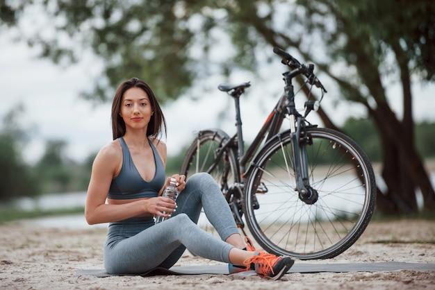 Vergessen sie nicht, wasser für ihre übungen zu nehmen. weibliche radfahrerin mit guter körperform, die tagsüber nahe ihrem fahrrad am strand sitzt