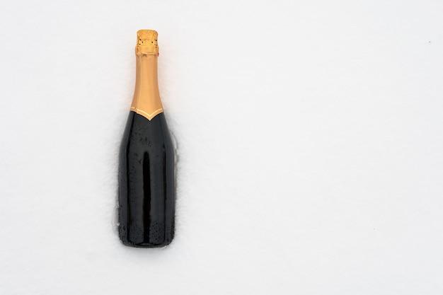 Vergessene flasche im schnee. grüne geschlossene flasche ohne etikett. platz für text auf der linken seite. exemplar.