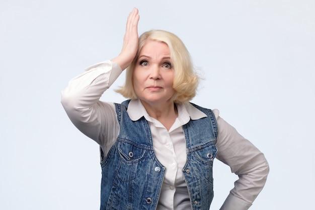 Vergessliche ältere blonde frau, die ihren kopf kratzt
