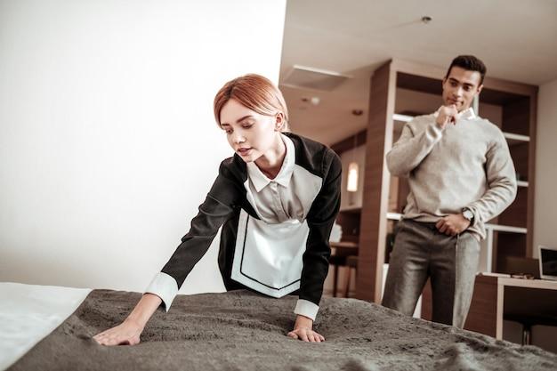 Vergewaltiger im hotel. vergewaltiger mit unangenehmem aussehen, der im hotel lebt und beobachtet, wie das dienstmädchen sein bett macht