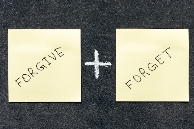 Vergib und vergiss wörter, die handgeschrieben auf aufklebernotizen sind