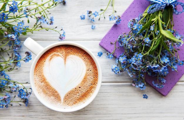 Vergiss mich nicht blumen, kaffee und notizbuch