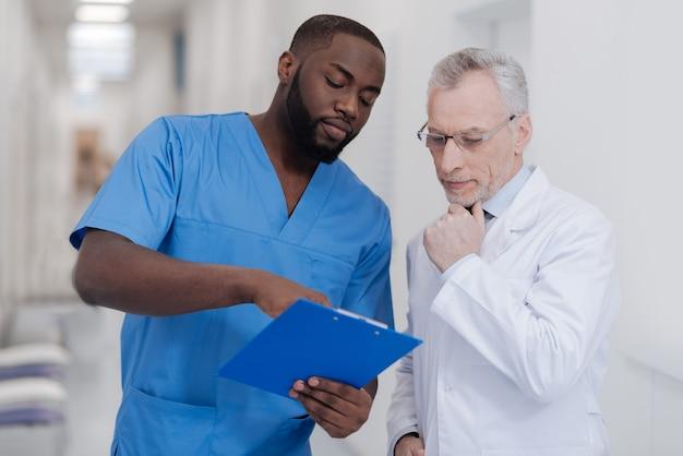 Vergleich unserer erfahrungen. junger ehrgeiziger afroamerikanischer arzt, der im krankenhaus steht, während ordner hält und meinungen mit gealtertem kollegen teilt