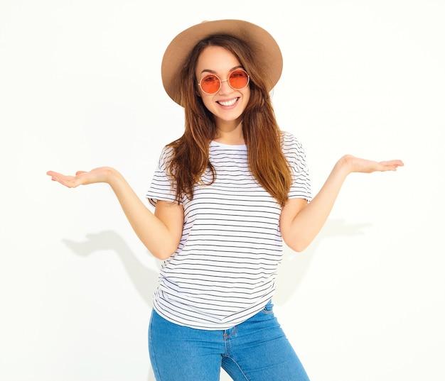 Vergleichskonzept. junge brunettefrau in der zufälligen hippie-kleidung und in braunem hut, die etwas auf beiden flachen händen anzeigen