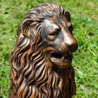 Vergoldete skulptur eines löwenkopfes in einem park auf dem grünen gras
