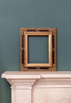 Vergoldeter oder goldener leerer rechteckiger vintage-rahmen auf einem kaminsims für ein bild oder gemälde, das an eine grüne wand gelehnt ist