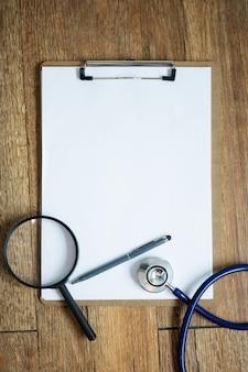 Vergrößerungsglas mit stethoskop auf leerem notizbuch auf tabelle. konzept des medizinischen hintergrundes