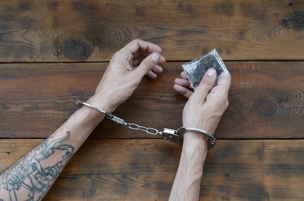 Verhaftete drogendealerhände in polizeihandschellen mit kleinem hash-drogenpaket auf dunklem holztischhintergrund