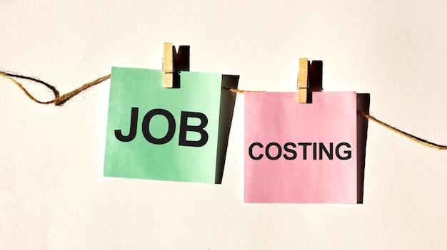 Verhaltenskodex textwörter job costing auf gelber aufklebernotiz auf weißer wand oder tisch.