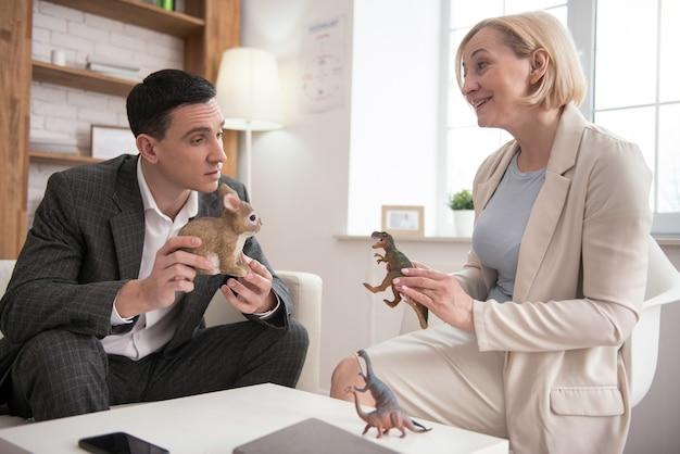 Verhaltensschema. junger mann, der spielzeug trägt, während er mit glücklichem reifem psychologen spricht