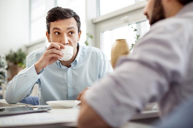 Verhandeln. attraktiver, konzentrierter, dunkeläugiger mann, der mit seinem partner spricht, der neben ihm sitzt und kaffee trinkt