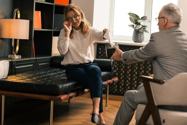 Verheiratete frau in brille weint, während sie sich über ihre probleme in einem psychotherapeutenbüro beschwert