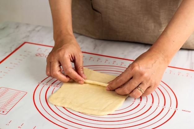 Verheiratete frau mit ring an der linken hand, die rohen brotteig faltet, backprozess, der pizza oder brot macht