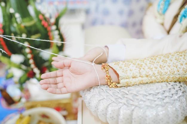 Verheiratete paare banden das handgelenk, traditionelle thailändische hochzeitszeremonie, hochzeitszeremonie in thailand.