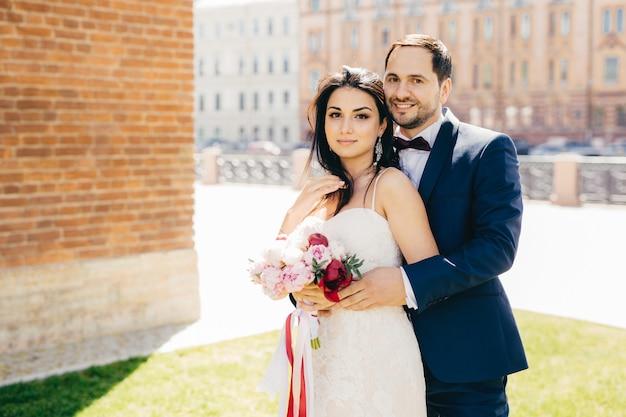 Verheiratete paare mit glücklichen ausdrücken stehen nahe beieinander und umarmen sich leidenschaftlich