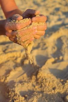 Verheirateter mann mit sand in den händen. sonnenuntergangszeit