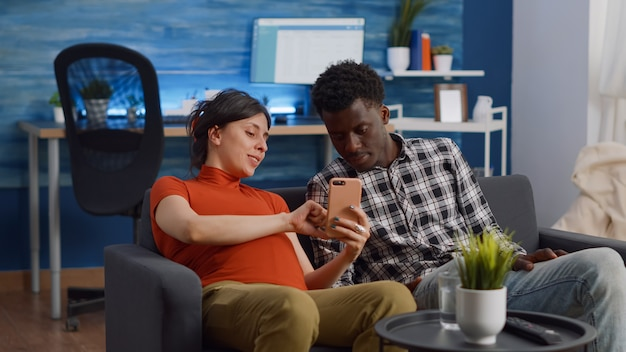Verheiratetes interracial paar entspannt sich auf dem sofa im wohnzimmer
