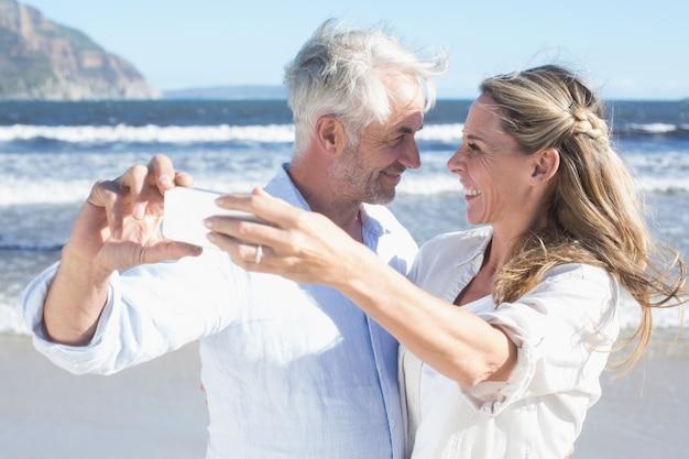 Verheiratetes paar am strand, der zusammen ein selfie nimmt
