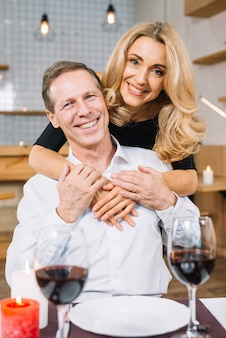 Verheiratetes paar, das die kamera umarmt und gegenüberstellt