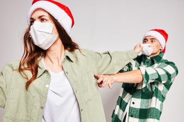 Verheiratetes paar, das medizinische maskenweihnachtsfreundschaftskommunikation trägt