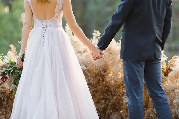Verheiratetes paar, das zurück steht und hände anhält