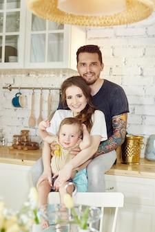 Verheiratetes paar und ihr kleines baby baby in ihren armen. junge familie zu hause morgens an einem freien tag. freudige und fröhliche gesichter, die sich umarmen und spaß haben