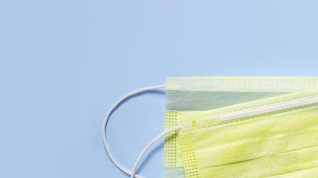 Verhindern sie coronavirus. gelbe medizinische maske, medizinische schutzmaske lokalisiert auf blauem hintergrund. einweg-gesichtsmaske. coronavirus-hygienekonzept