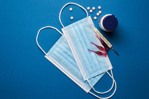Verhindern sie coronavirus. medizinische maske, thermometer, vitamine, spritze auf blauem hintergrund.