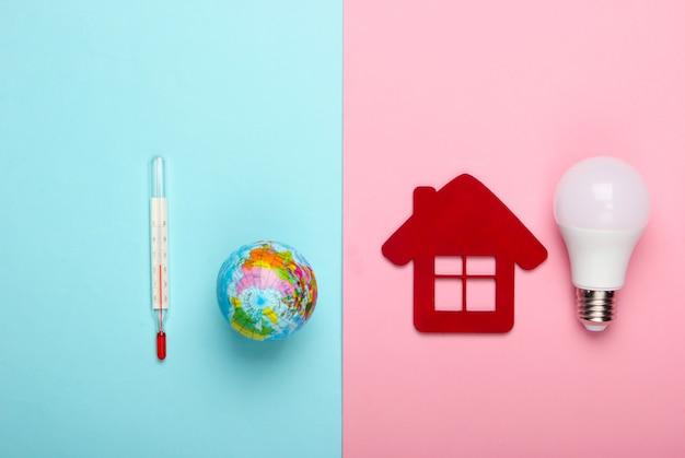 Verhinderung der globalen erwärmung. öko, energiesparkonzept. figur des hauses mit led-glühbirne, globus mit einem thermometer auf einem blau-rosa pastellhintergrund.
