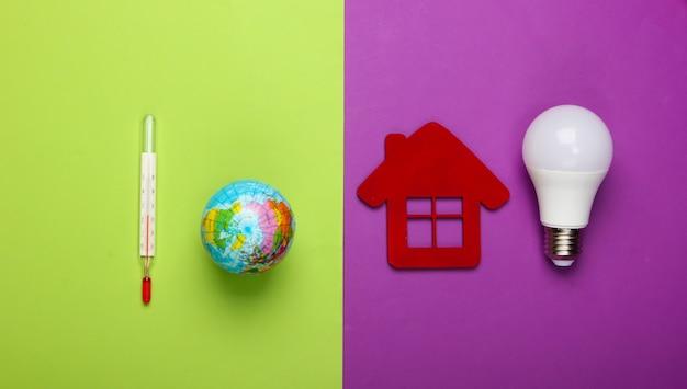 Verhinderung der globalen erwärmung. öko, energiesparkonzept. figur des hauses mit led-glühbirne, globus mit einem thermometer auf grünem lila hintergrund.