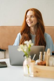 Verical mittleres schussporträt einer lächelnden jungen frau, die mit einem laptop am tisch im gemütlichen café sitzt und wegschaut. hübsche kaukasische dame der rothaarigen entfernt, die arbeitet oder studiert.