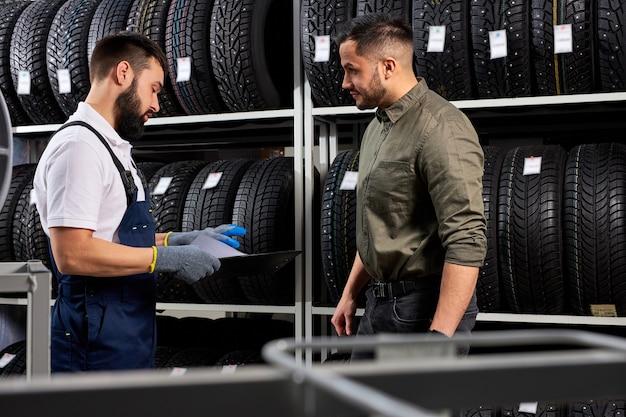 Verkäufer automechaniker hilft mann bei der auswahl der reifen im autohaus, zeigt und gibt informationen über die besten