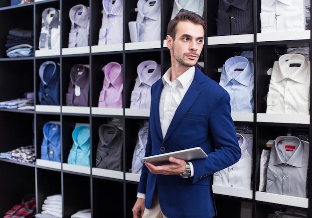 Verkäufer boutique herrenbekleidung, die an einem tablett im hintergrundstand mit hemden arbeitet