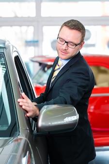 Verkäufer, der auto an der verkaufsstelle verkauft