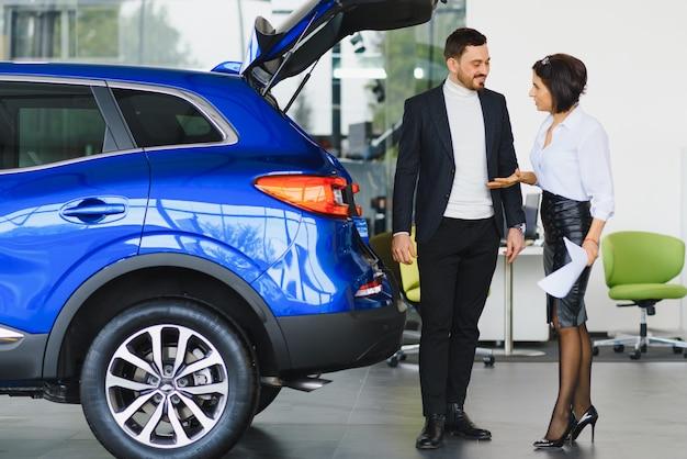 Verkäufer, der autos beim autohaus verkauft