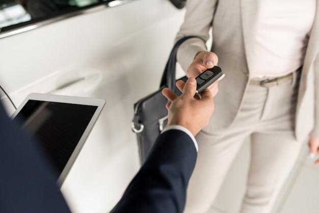 Verkäufer, der dem kunden autoschlüssel gibt